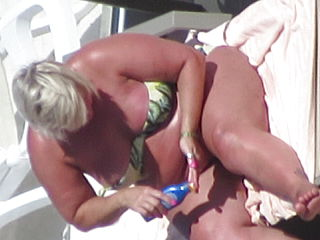 Bbw GILF in swimsuit nip-slip while tanning on the beach