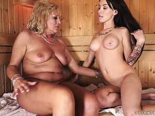 Older and youthful gal in the sauna take turns slurping muff and frigging