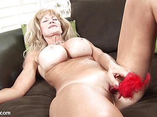 Busty old whore sticks hard toy in her snatch