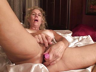 Mature whore sticks hard toy in her cunt