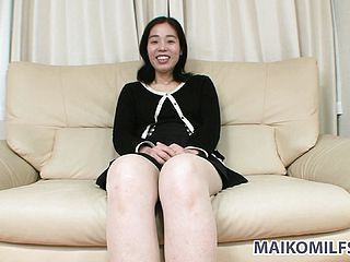 Sultry Japanese cougar sits on the couch, antsy to please her crazy sexual cravings
