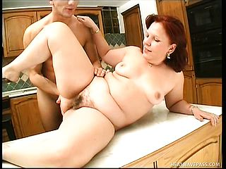 Redhead mummy with saggy boobies gets romped by a youthfull boy in the kitchen